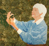 Older woman in blue blouse typing bits of yarn to cedar branches for the bush tits to build their nests with.