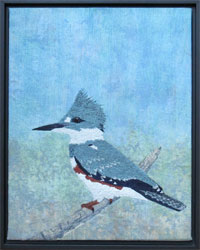 A thread painted kingfisher sitting on a piece of greying driftwood. Raw silk background sky inked and painted in soft blues and mauves with a hint of rocks at the base.